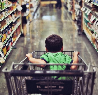 young boy in grocery cart