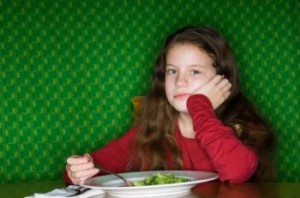 Girl pondering broccoli