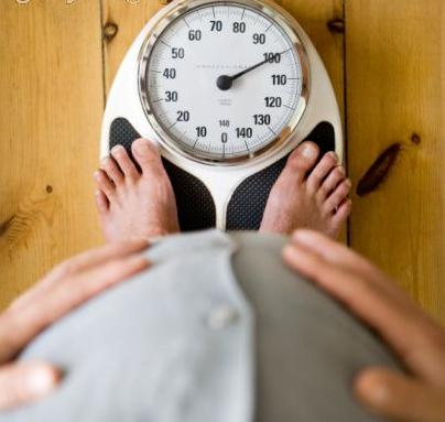 man with belly on weighing scale